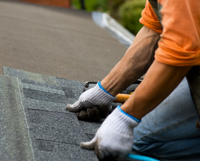 Row of Asphalt Roof Shingles Being Installed